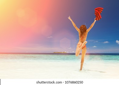 Happy young woman jumping on the beach. Happy lifestyle. White sand, blue sky, sun and crystal sea of tropical beach. Vacation at Paradise. Ocean beach relax, travel to islands. Sun light