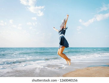 Happy young woman jumping on sand beach near the sea on vacations.