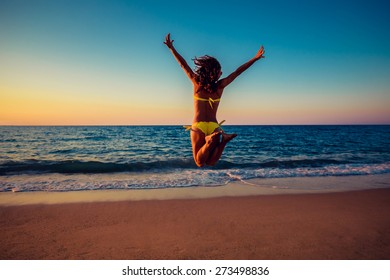 Happy young woman jumping on the beach. Summer vacation and freedom concept