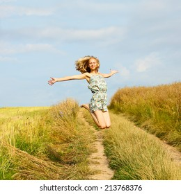 Happy Young Woman Jumping over blue sky. The concept of joy and happiness