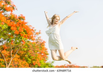 Happy young woman jumping at the park.