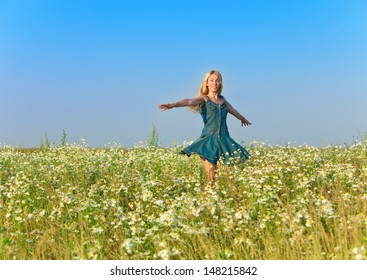 The happy young woman jumps in the field  of chamomiles