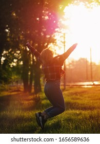 Happy young woman jumps at sunset and enjoys life