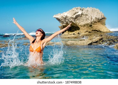 Happy young woman jumps in water against awesome rocky beach. Shot in De Hoop Nature Reserve, Western Cape, South Africa.
