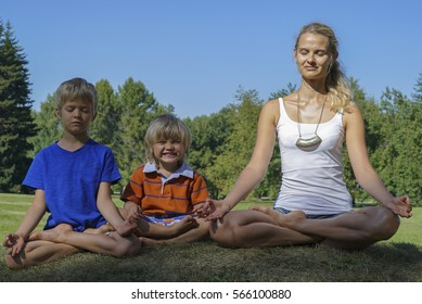 Happy young woman with kids meditates in green park at sunny summer day.