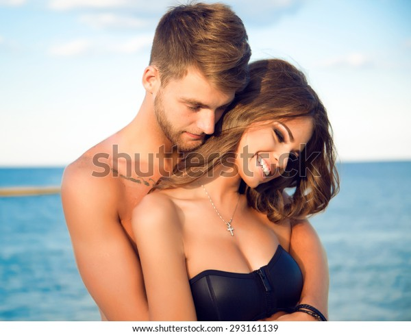 Happy young woman kissing her handsome boyfriend,enjoy their summer vacation on amazing beach,lifestyle portrait of stylish hipster couple in love.positive emotions.holding hands,people in love,smiley