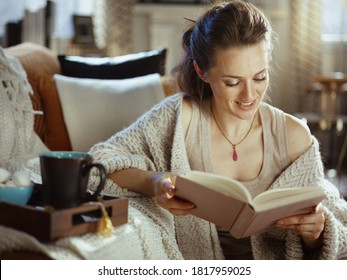 happy young woman in knitted cosy cardigan with tray and cup reading book at modern home in sunny autumn day.