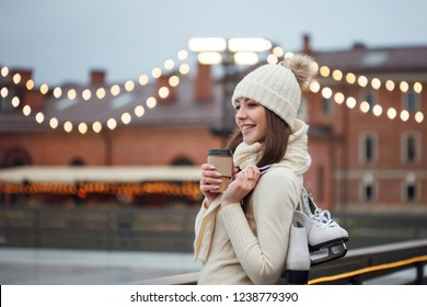 Happy young woman in knitted sweater and hat is going skating. Young brunette with skates on her shoulder, city Park in winter, ice rink