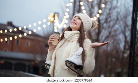 Happy young woman in knitted sweater and hat is going skating and drinks coffee. Young brunette with skates on her shoulder, city Park in winter, ice rink