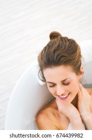 happy young woman laying in bathtub