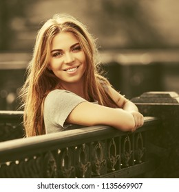Happy young woman leaning on the railing Stylish fashion model wearing grey t-shirt outdoor