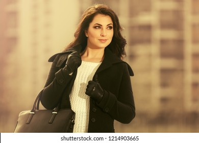 Happy young woman with leather handbag walking in city street Stylish fashion model wearing classic black coat and white pullover