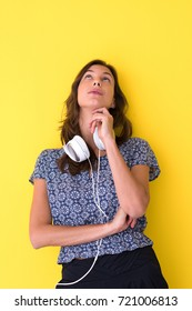 Happy young woman listening and enjoying music with headphones isolated on a yellow background
