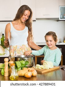 Happy young woman with little child cooking soup at home kitchen