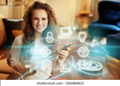 happy young woman with long brunette hair with coffee cup using smart home application on smartphone and robot vacuum cleaning floor in background in the modern living room.