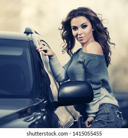 Happy young woman with long curly hairs next to her car  Stylish fashion model in blue jeans and pullover