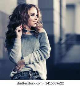 Happy young woman with long curly hairs walking on city street Stylish fashion model in gray blue pullover and jeans