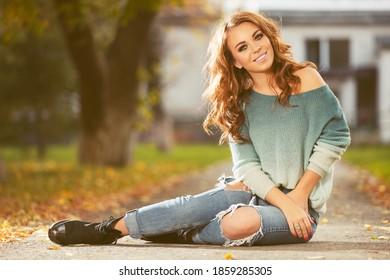 Fröhliche junge Frau mit langen, lockigen Haaren, die auf dem Bürgersteig sitzen Stilvolles Modemodell in blauem Pullover und gerippter Jeans