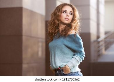Fröhliche junge Frau mit langen, lockigen Haaren auf der Stadtstraße Stilvolles Modemodell in blauem Pullover