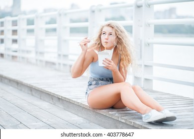 Happy young woman with long curly hair, sitting on the wooden floor, holding a lunch box and eating up noodles from Chinese take-out with chopsticks.