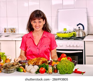 Happy young woman with long hair cooking chicken at home kitchen.