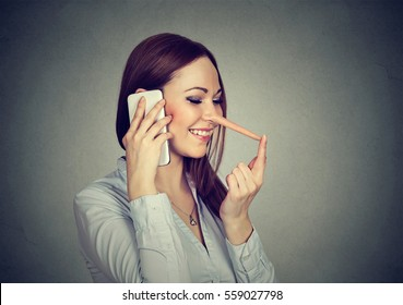 Happy young woman with long nose talking on mobile phone isolated on gray wall background. Liar concept. Human emotion feelings, character traits