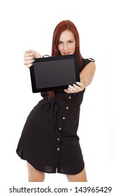 A happy young woman with long red hair smiles while holding a tablet computer.