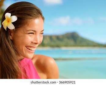 Happy young woman looking away at beach. Attractive female is with frangipani flower in her hair. Beautiful tourist is enjoying her vacation.
