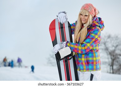 Happy young woman looking away while holding snowboard in snow