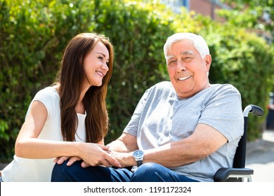 Happy Young Woman Looking At Her Father Sitting On Wheelchair At Outdoors