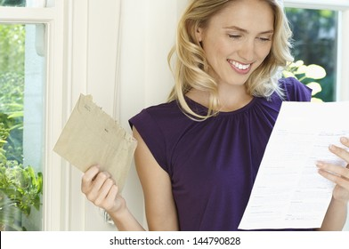 Happy young woman looking at letter in home