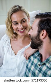 Happy young woman looking at man while sitting on sofa