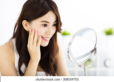 Happy young woman  looking on mirror