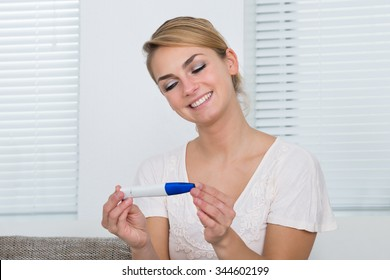 Happy young woman looking at pregnancy result at home