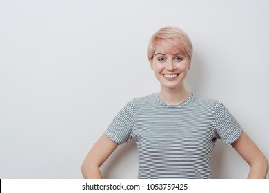 Happy young woman with a lovely warm smile and modern short haircut posing over a white wall background with copy space