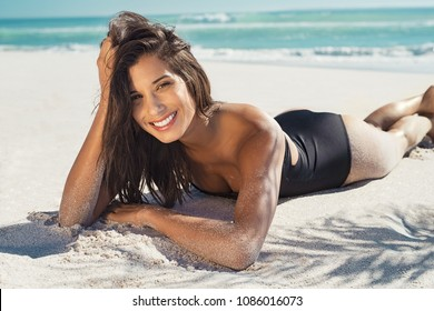 Happy young woman lying on white sand and looking at camera. Portrait of beautiful woman lying on front at tropical beach. Brunette girl in black swimsuit relaxing at sea under the palm trees.
