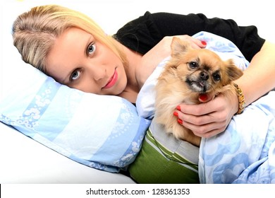 A happy young woman lying on her bed with her puppy.