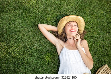 Happy young woman lying on green grass and dreaming. copy space, view from above, soft