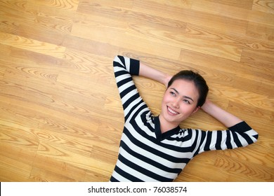 happy young woman lying on wooden parquet floor relaxed at home looking up