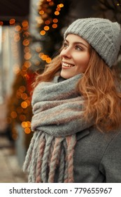 Happy young woman with a magic smile in fashion stylish knitwear clothes with a knitted gray hat and scarf near the lights on a holidays