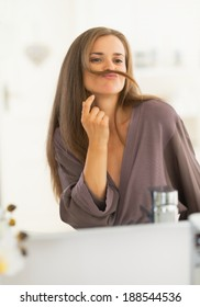 Happy young woman making mustache with hair