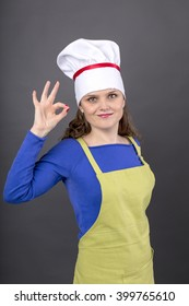 Happy young woman  making OK sign over gray background