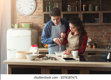 Happy young woman and man baking pie in loft kitchen. Young family cooking at home.