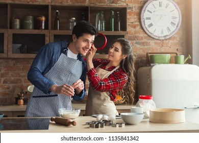 Happy young woman and man baking pie and having fun in loft kitchen. Young family cooking at home, woman sharing with man headphones with music, copy space