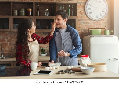 Happy young woman and man baking pie and having fun in loft kitchen. Young family cooking at home together, copy space