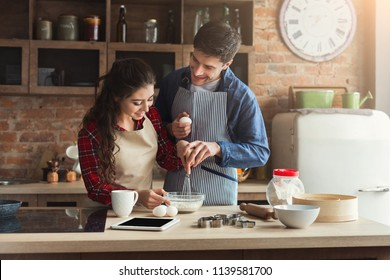 Happy young woman and man baking pie and having fun in loft kitchen. Young family cooking at home, using digital tablet. Mockup for recipe