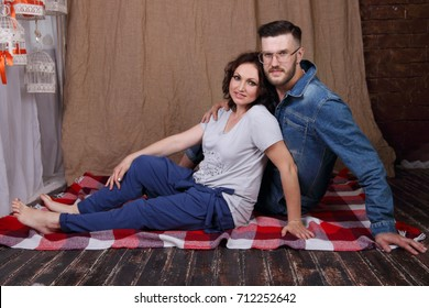 Happy young woman and man in glasses sit on plaid on floor in studio