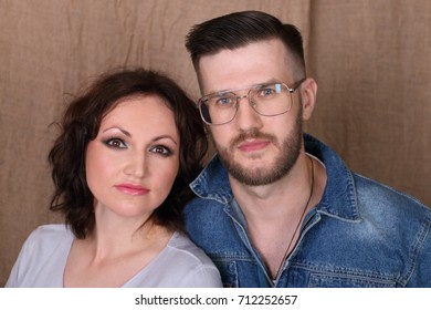 Happy young woman and man in glasses pose together in studio