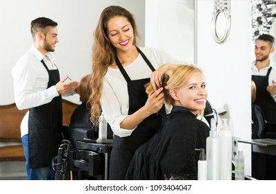 Happy young woman and man hairdresser doing hairstyle for young men
