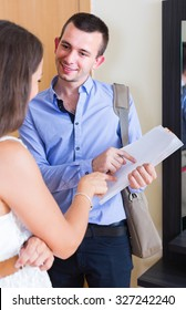 Happy young woman and man standing with official papers near door